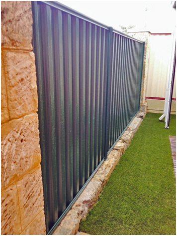 Colourbond fence installed into natural limestone blocks