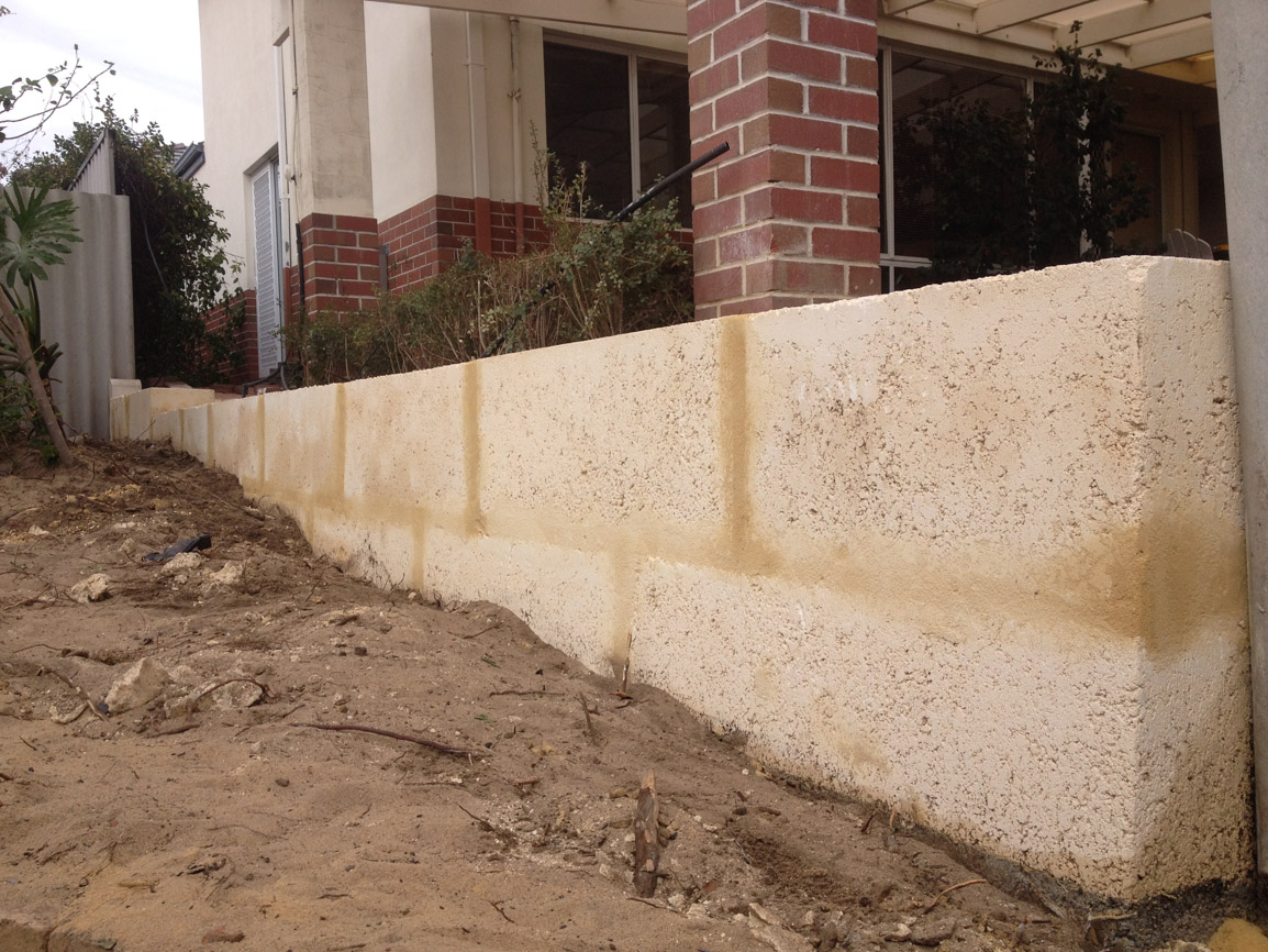 1 metre reconstituted limestone block retaing wall contractor and colorbond fence core drilled on top